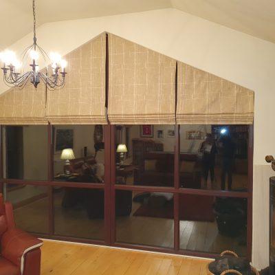 Villanova fabric Roman blinds on an apex window